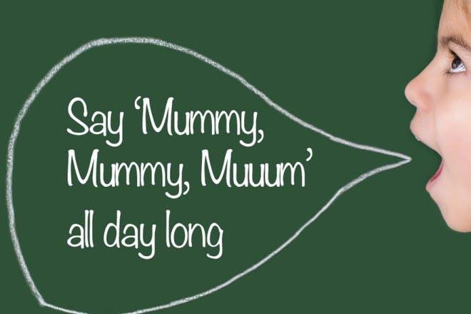child saying mum in front of blackboard