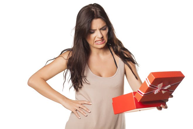 woman pulling an unhappy face after opening a present box