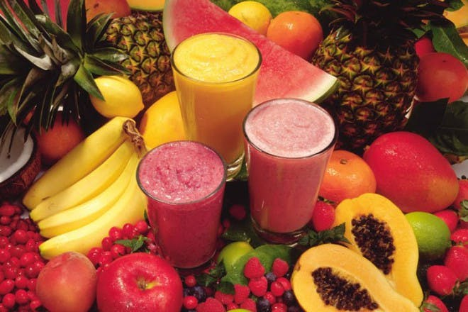 colourful smoothies surrounded by fruit