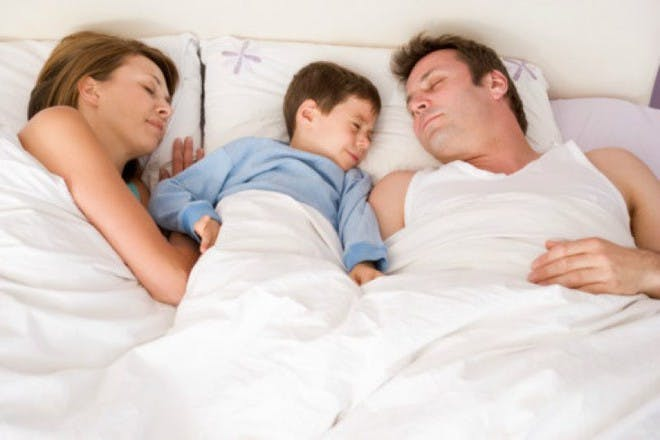 parents and child sleeping in bed