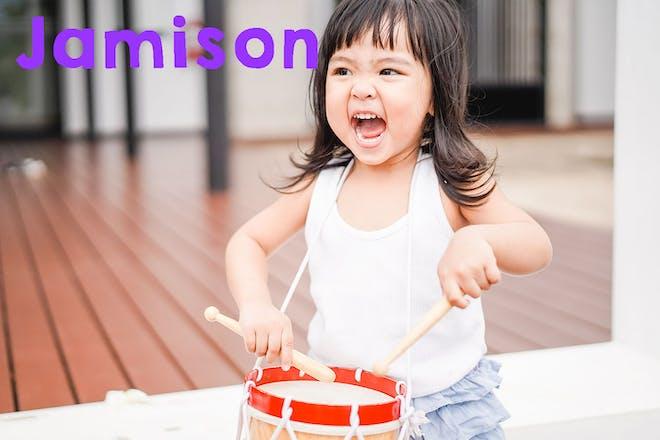 Toddler girl playing drum. Text says Jamison