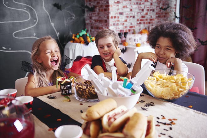 Kids dressed in Halloween costumes laughing at the table