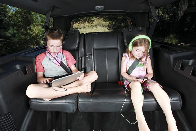 Kids with devices on the backseat of a car