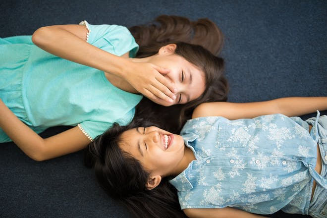 Two 10 year old girls lying down laughing