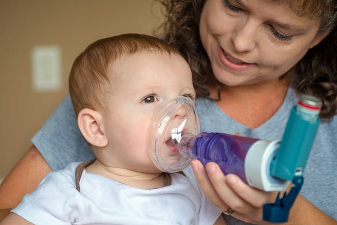 Child sitting on mum's lap being given asthma inhaler with spacer