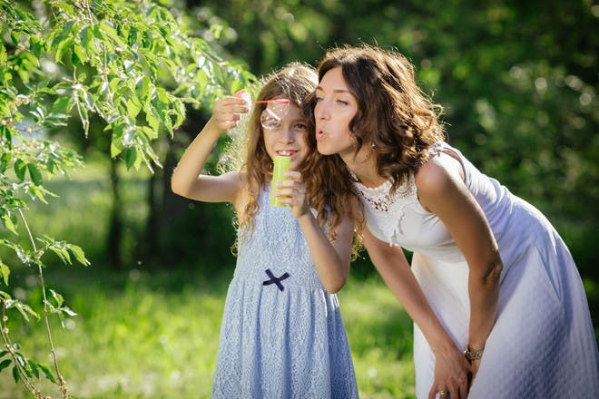 Mum blowing bubbles with girl
