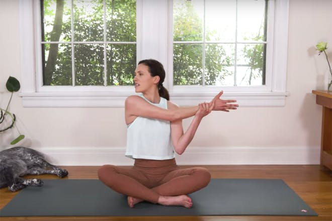 Still from Yoga with Adrienne video showing instructor stretching her arm across body