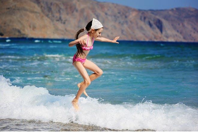 girl jumping in ocean