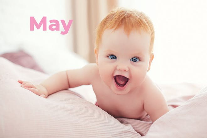Baby with red hair laughing at camera. Name May written in text