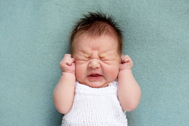 baby with hands scrunched up beside face