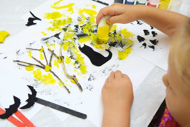 A toddler paints a Halloween haunted forest scene using twigs, cat and bat silhouettes cut from black paper, and black and yellow sponge painting