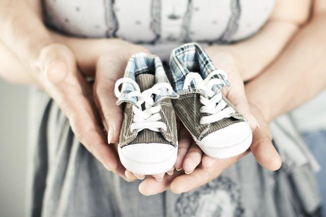 newborn baby boots in parents hands