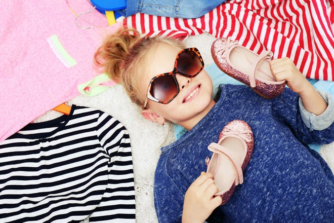 girl lying down surrounded by clothes