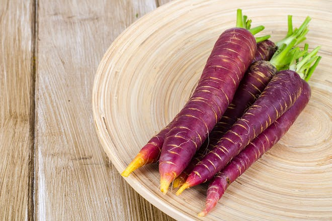 Five purple carrots on a wooden dish