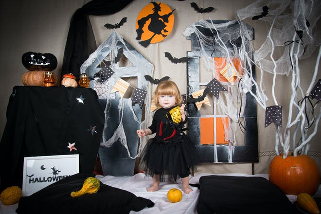 Toddler dressed in a black witch's dress surrounded by Halloween decorations