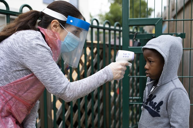 Child's temperature being checked at school gates
