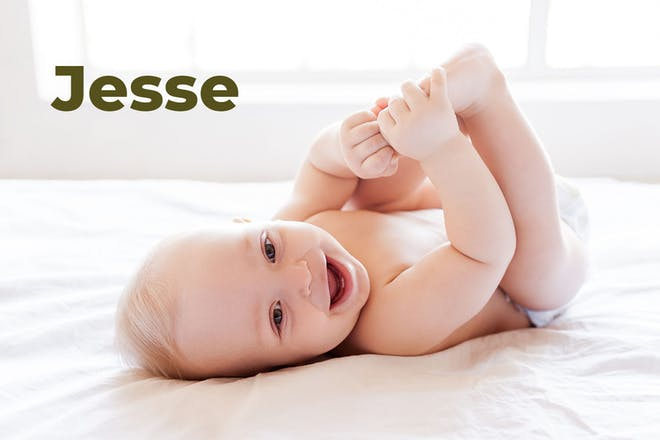 Baby lying on back laughing and holding feet. Name Jesse written in text