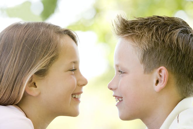 boy and girl facing each other laughing