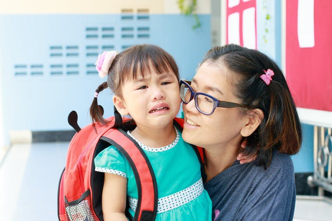 Mum saying goodbye to crying daughter at childcare