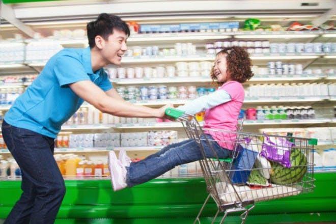 man pushing girl in trolley in shop