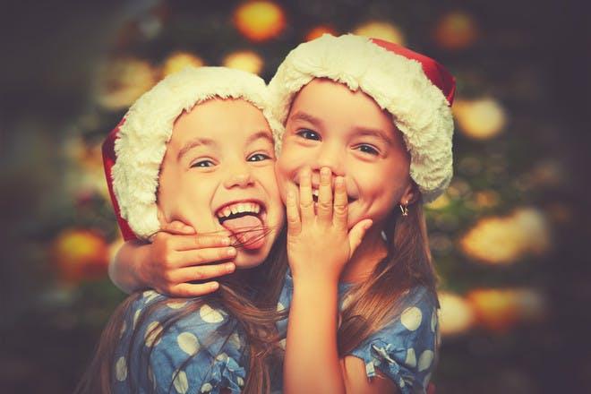 two girls wearing christmas hats hugging