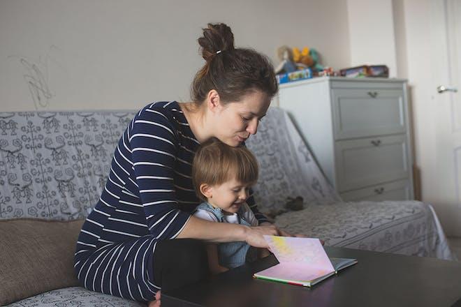 Pregnant mum reading to toddler