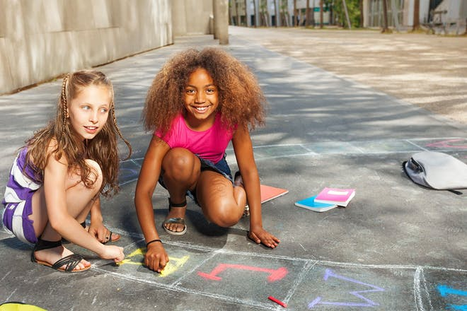 two girls drawing chalk letters on floor