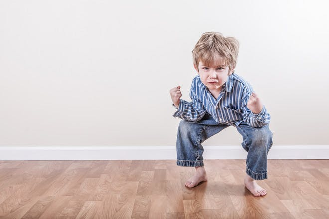 boy crouching with pained expression