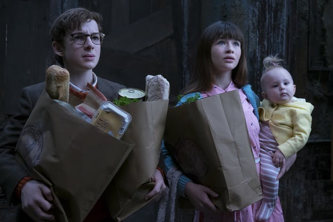 production still from Netflix A Series of Unfortunate Events - the Baudelaire children carrying food shopping