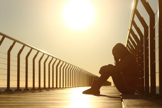Teen girl sitting on bridge