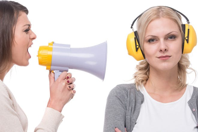 Woman shouting through megaphone at another woman wearing headphones