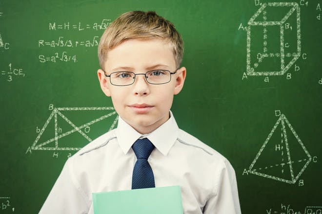 Child with glasses and tie in front of blackboard