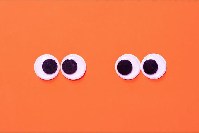 Craft googly eyes against bright orange background