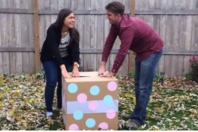 Man and woman with gender reveal box