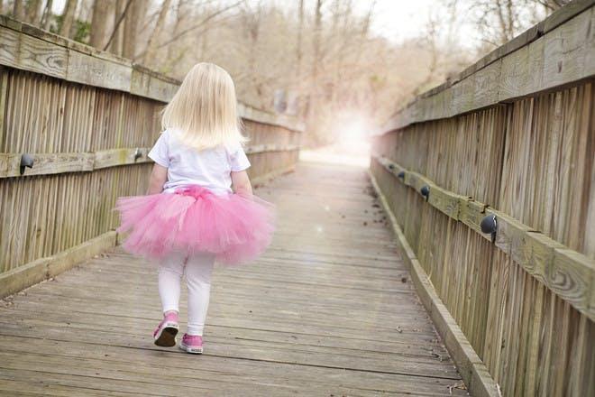 toddler in pink tutu walking on wooden bridge