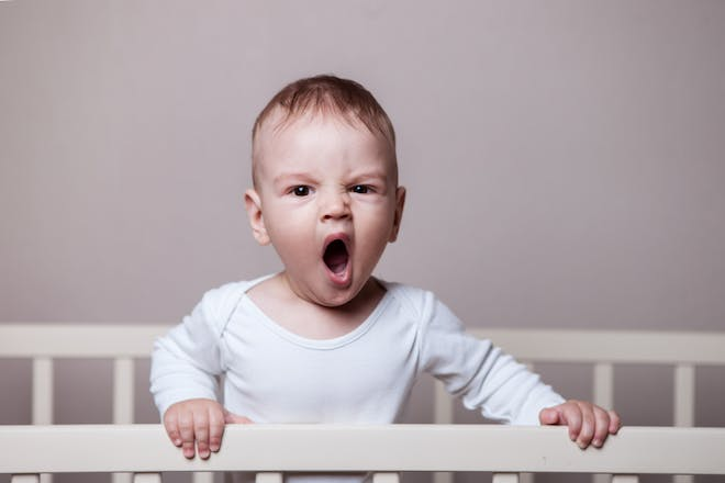 yawning baby in cot