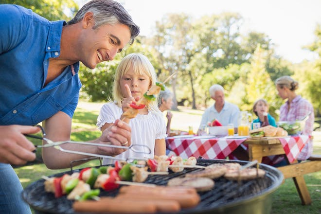 Man and daughter barbecuing
