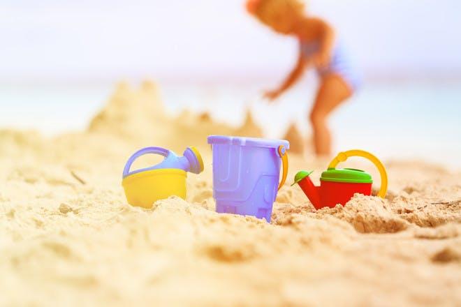 little girl building sandcastles on beach