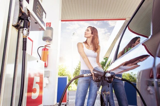 Woman putting petrol into car