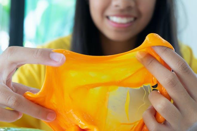 Girl holding homemade orange slime