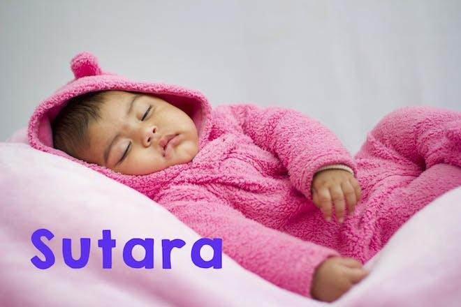 Baby girl wearing pink pyjamas and sleeping