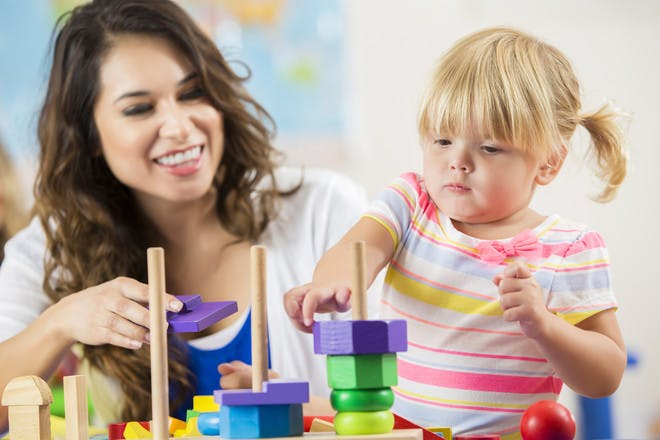 little girl with key worker at nursery