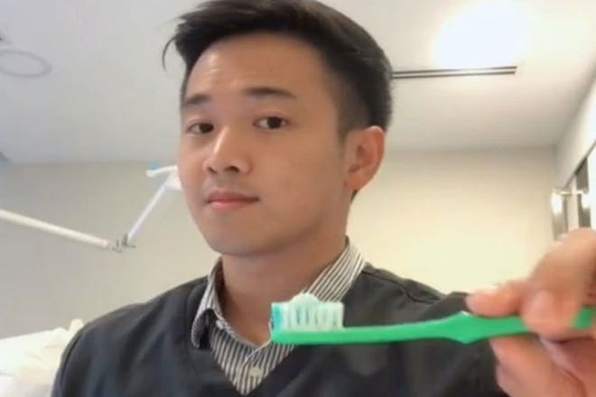 A dentist showing a pea-sized amount of toothpaste on a toothbrush
