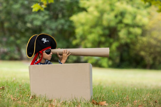 boy sitting in a box in the park dressed as a pirate