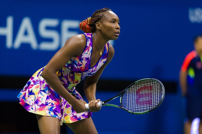 Venus Williams playing tennis in brightly coloured outfit