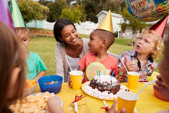 Four year old's birthday party with children sitting round party table and cake