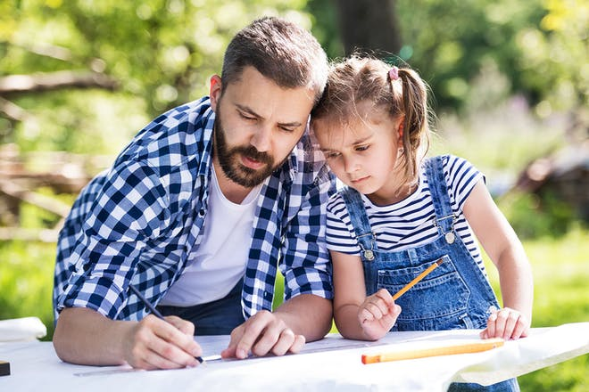 Dad and daughter writing a plan on a big piece if paper in the garden