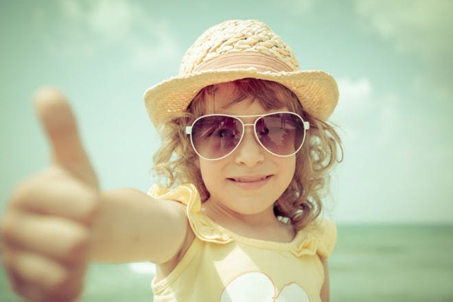 girl at the beach with sunhat and shades giving thumbs up