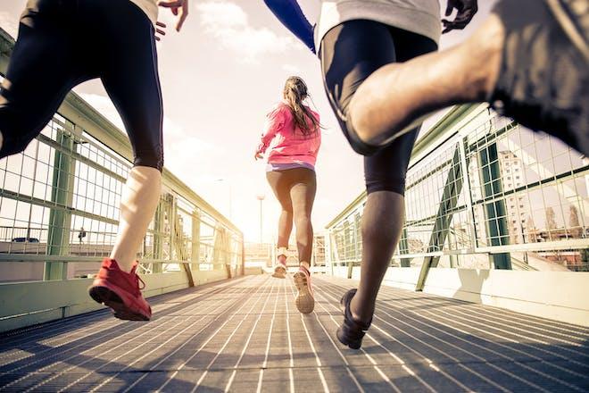 Three people running on a bridge