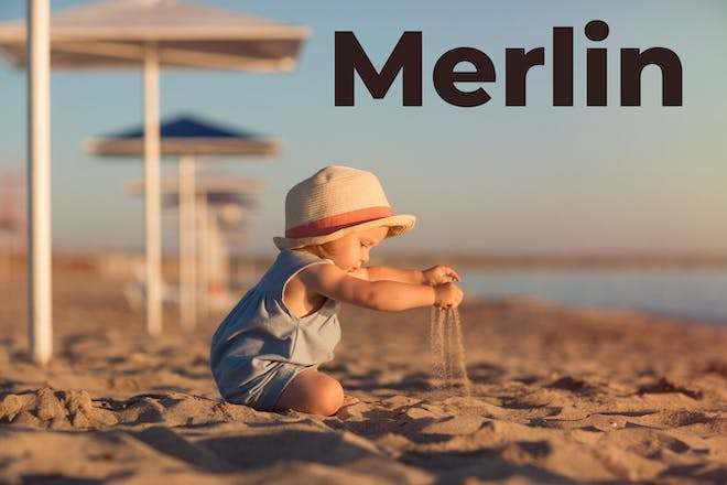 Baby on the beach with Merlin written in text